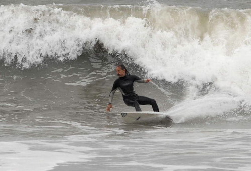 Surfer in wetsuit on wave, surfing backhand