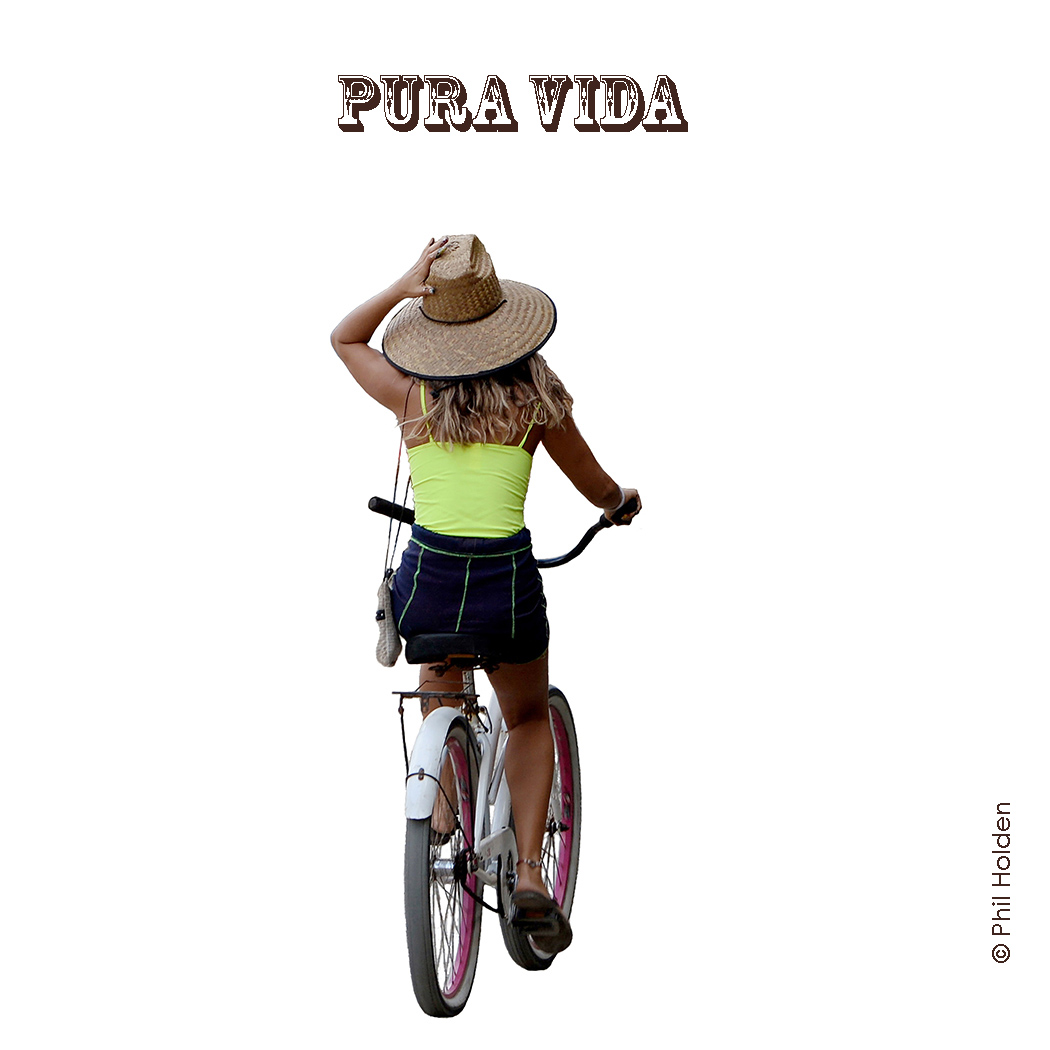 Girl on bicycle holding onto hat