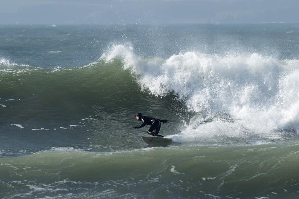 surfer bottom turning at base of huge wave