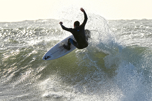 a surfer flies off the lip of the wave